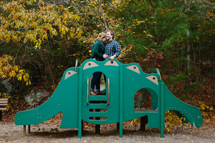 Breakheart engagement photo on playground with dinosaur